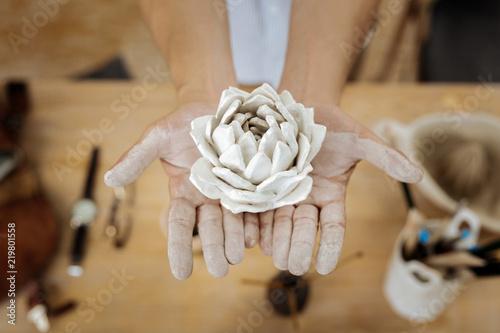 Foto Murales Showing flower. Creative famous handicraftsman showing amazing earthenware flower in his hands