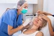 Leinwandbild Motiv Senior woman getting facial injection