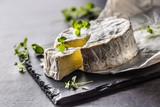 Cheese camambert from oregano herbs on slate board - 219814791