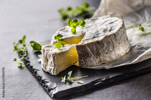 Fototapeta Cheese camambert from oregano herbs on slate board
