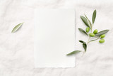 feminine minimalist styled wedding stationery  mockup with a blank invitation card (portrait format) and a fresh olive twig on a white soft linen background, flat lay / top view - 219821140