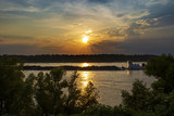 A towboat with barges in the Mississippi river at sunset near the city of Vicksburg in the State of Mississippi, USA. - 219823778