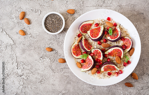 Leinwanddruck Bild Delicious and healthy oatmeal with figs, almond and chia seeds. Healthy breakfast. Fitness food. Proper nutrition. Flat lay. Top view.