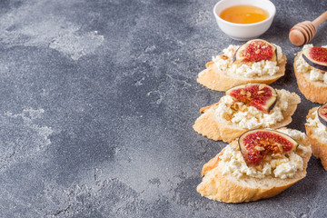 Snacks bruschetta with cottage cheese, walnut and honey and figs