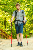young man with backpack hiking in forest trail - 219847158