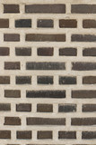 the textured wall of brownish and gray brick
