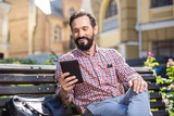 Smiling happy man reading his e-book outdoors - 219854552
