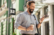 Positive adult man drinking coffee on his way to work