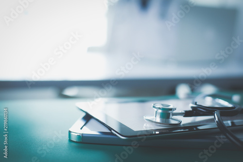Foto Murales Medical equipment: blue stethoscope and tablet on white background. Medical equipment