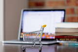 Little supermarket cart on a table with laptop computer and books on brick wall background - 219862182