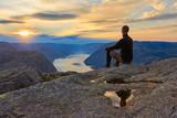 Mann sitzt auf dem Berggipfel nach vollendeter Wanderung mit Blick in Richtung Sonnenaufgang - 219863706