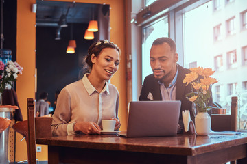 Attractive African-American couple at a business meeting in the restaurant discussing working moments with laptop at lunchtime. © Fxquadro