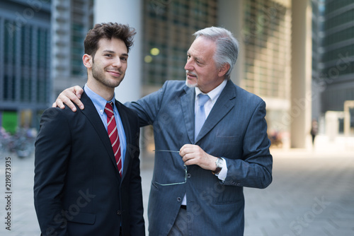 Leinwanddruck Bild Portrait of a confident senior businessman talking to a younger colleague