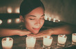 Leinwanddruck Bild - Spa luxury jacuzzi woman relaxing in whirlpool hot tub with water massaging jets. Woman in candlelight enjoying hydrotherapy in private massage pool. Hotel lifestyle.
