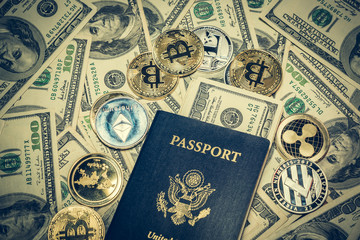 Crypto coins on one hundred dollar bills and United States passport