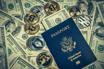 Cryptocurrency coins on one hundred dollar bills and american passport