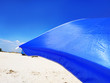 Leinwanddruck Bild - Sun Beach Umbrella Parasol on Sunny Day on Background of a Blue Sky Giving Shade and Protection