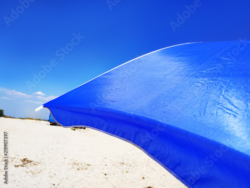 Leinwanddruck Bild Sun Beach Umbrella Parasol on Sunny Day on Background of a Blue Sky Giving Shade and Protection