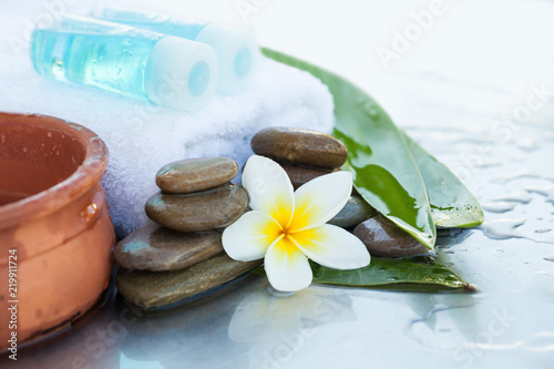Leinwanddruck Bild Two bottles with oil for massage. Spa concept with flowers and leaves