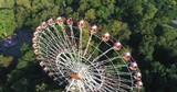 Amusement park, Ferris wheel in the city center, drone shot, view from height. - 219913317