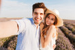 Beautiful young couple taking a selfie while hugging