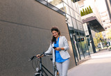 Young businesswoman going to work with his bicycle.