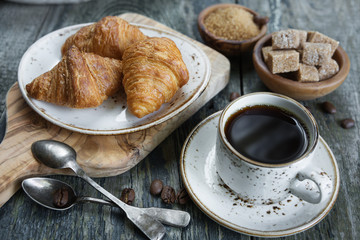 Cup of black coffee and croissants