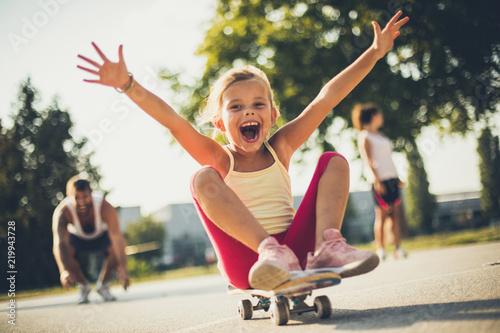Little girl on skateboard . Parents behind.