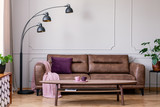Purple pillow and pastel pink blanket placed on leather couch in real photo of bright sitting room interior with metal lamp, coffee table with tea cups and wainscoting on wall - 219957370