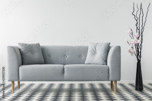 Flowers Next To Grey Sofa With Cushions In Minimal Living Room Interior  With Patterned Floor.