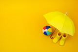 A pair of yellow rain boots and a umbrella and ball on a yellow - 219958342