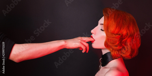 Fotoboard na płycie - Kinky redhead girl with bondage suck finger on black background. Sexual bdsm toy. Attire for playing bdsm games. Kinky lady with bondage with chain around neck. Lips suck male finger