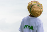 Black adult male Rastafarian with dreadlocks in knitted tam wearing white t-shirt marked Official at athletic event