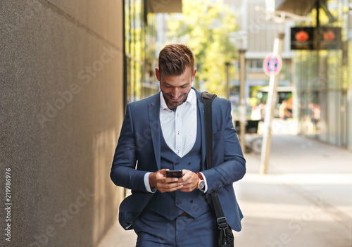 Businessman looking at his mobile phone while walking on street to office.