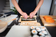 Woman making at home Japanese sushi rolls