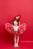 A small girl in Little Red Riding Hood costume in studio on a red background. - 220001134