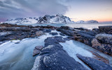 Seashore with stones and ice during sunset. Beautiful natural seascape in the Lofoten islands, Norway. Sea and mountains at the winter - 220005937