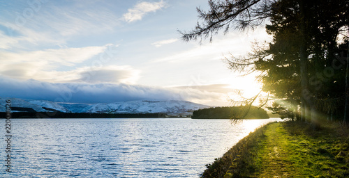 lake side panorama of distant snow covered mountain at sunset - 220008126