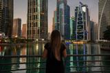 Girl watching skyscrapers on sunset near lake