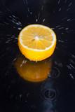 Splashing water against a tasty lemon on a black background