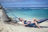 Woman relaxing in hammock on beach - 220035785