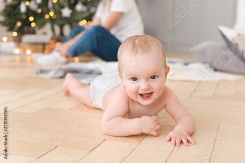 Leinwanddruck Bild Smiling naked baby lying on floor and looking at camera on blurred background of Christmas tree in lights and mother wrapping presents