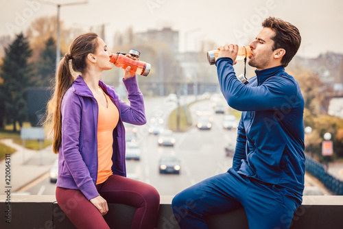 Leinwanddruck Bild Woman and man drinking water in break from fitness training with a cityscape in the background