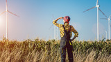 Farmer woman has invested not only in land but also wind energy watching the turbines