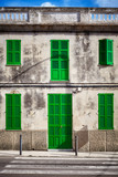 Mediterranean style old stone building facade with green door and shutters, Mallorca, Spain. - 220065119