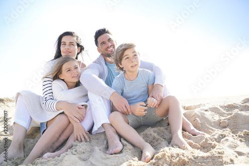 Foto Murales Family sitting on the beach in late afternoon