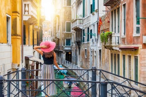 Fototapeta Elegante, reisende Frau mit rotem Sonnenhut steht auf einer Brücke in Venedig und genießt den Blick auf einen Kanal, Italien