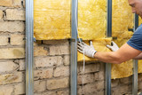 worker insulating old brick wall with glass wool sheets - 220070947