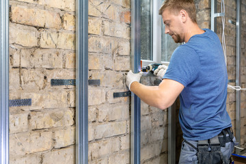 man installing metal profile frame on the old brick wall for plasterboard sheets