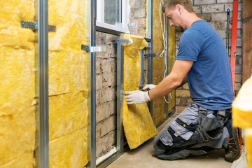 old house reconstruction - construction worker insulating brick wall with glass wool
